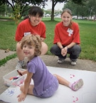 volunteers with kid at art camp