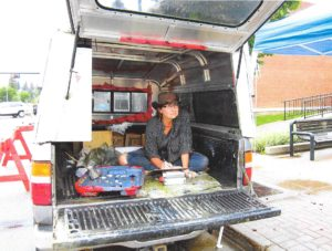 artist nicole bauberger in her truck-studio, painting on the road