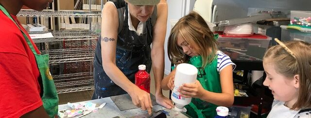 artist laurel paluck assists a young child with a printmaking project in the studio: they sqeeze inks out of a bottle while another student, and youth volunteer, look on.