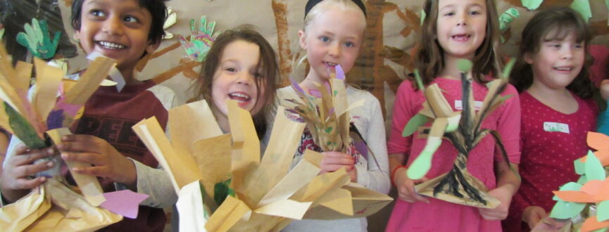Group of children holding up three dimensional paper sculptures made during an AGP camp