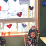 """A child sitting in front of a window decorated with colourful construction paper hearts and a sign that says: """"Thank you!"""""""