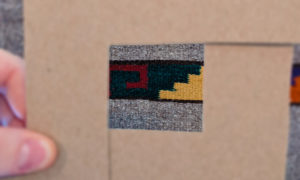 Grey, red, green, and yellow textile weave on a cardboard base