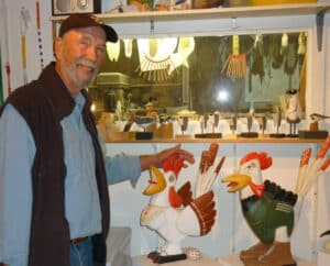 John Boorman in his studio with two rooster sculptures