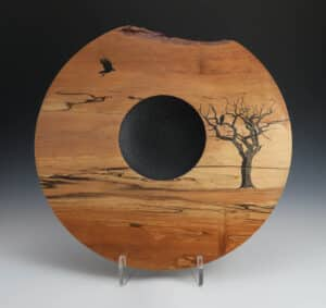 Barren tree and crow scene, burned into wooden face of a bowl, with black dimpled recess in the middle