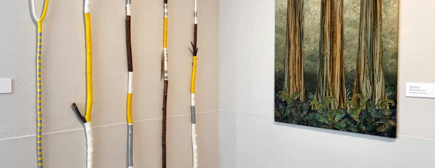 Left: John Boorman, walking sticks, painted carved wood; Right: Stephanie Ford Forrester, Ancestral Sisters #3, 2020, hand worked cotton and batiks
