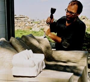 Ernest Daetwyler using model to carve limestone loveseat