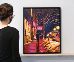 person on left viewing artwork featuring streetscape at night
