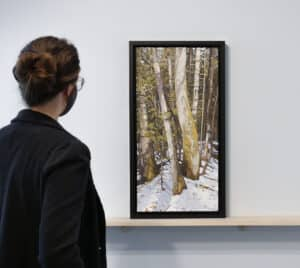 person on left looking at landscape painting on a ledge