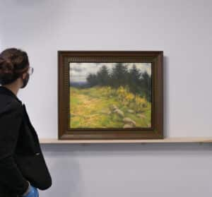 person on left looking at framed landscape painting on a ledge