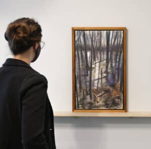 person on left looking at stylized landscape painting with trees