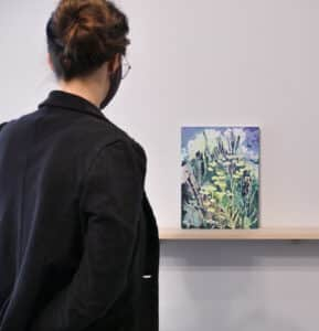 person on left viewing watercolour painting featuring florals in pastel shades