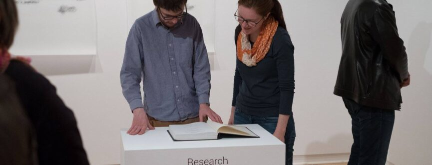 Two people reading a book on a white plinth installed in AGP's main gallery