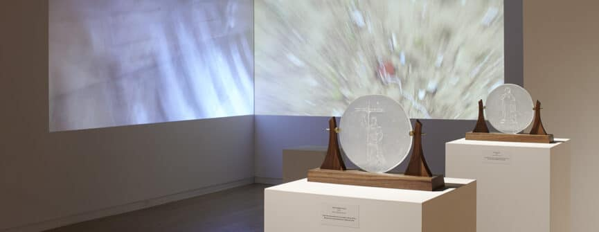 Bonnie Devine, From Left: La Rabida: the Sun and the Moon, 2016 Two channel projection, written, photographed, and directed by Bonnie Devine, edited by David DeLeary; Saint Junípero Serra, 2016, glass, Walnut, Brass; Cristóbal Colón, 2016, glass, walnut, brass. Photo by Michael Cullen, TPG Digital Arts, Toronto