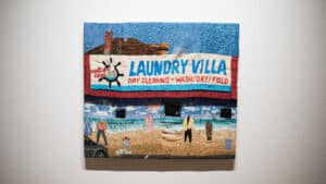 embroidered tapestry featuring a laundromat exterior