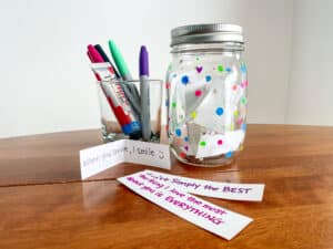 Image of markers, strips of paper, and a jar decorated with poladots