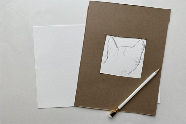 Pencil drawing of a cat head framed by a cardboard viewfinder