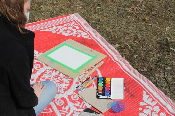 Person sitting outside on a red blanket with art supplies