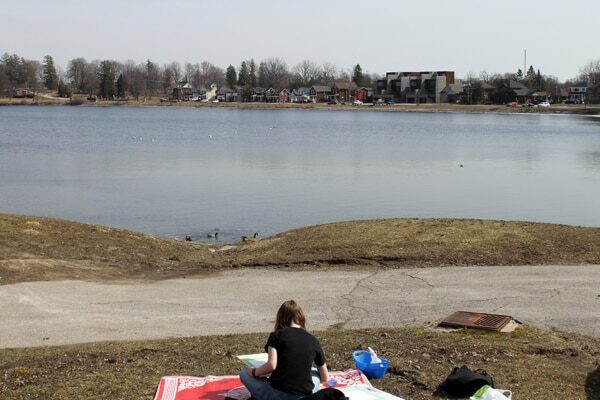 Person sitting outside on a red blanket by a lake with houses in the distance