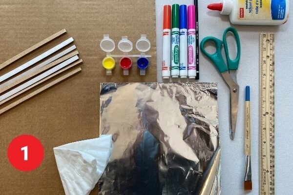 """Art supplies arranged on a table. Text reads """"1."""""""