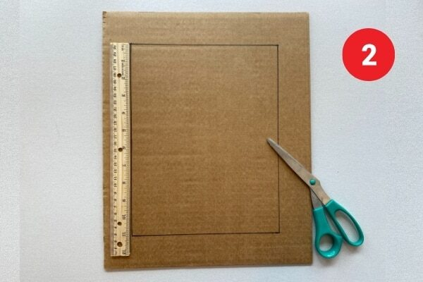 """Cardboard with a ruler and scissors. Text reads """"2."""""""