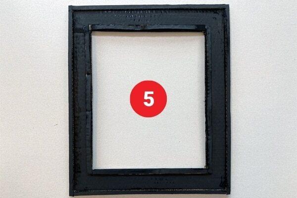 "Black rectangular cardboard frame. Text reads ""5."""