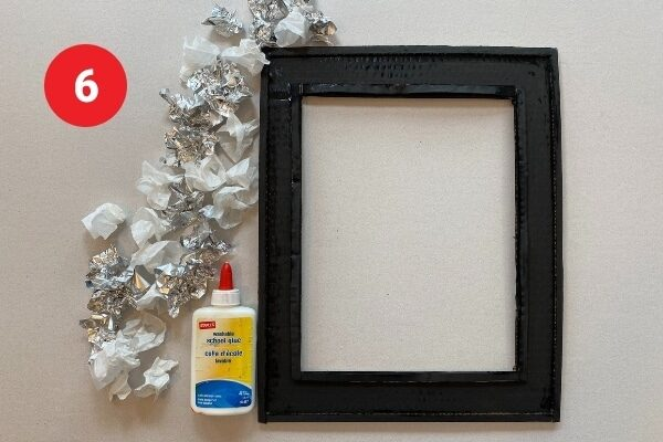 """Black rectangular cardboard frame with bottle of glue and a pile of tinfoil and paper flowers. Text reads """"6."""""""