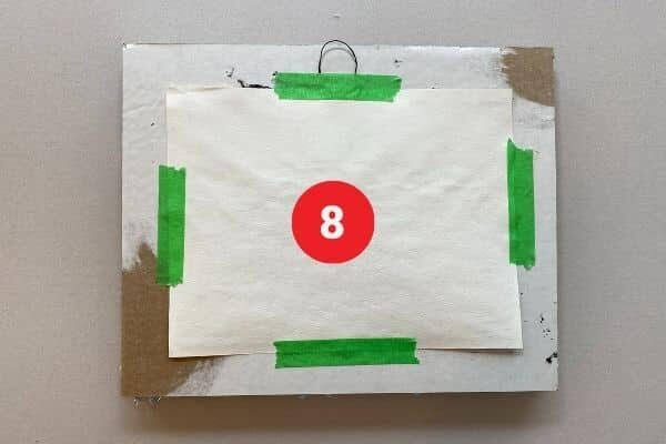 """The reverse side of a rectangular cardboard frame with a piece of paper taped to it with green painter's tape. Text reads """"8."""""""