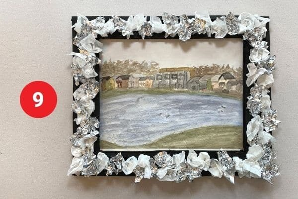 """Watercolour landscape painting with a black and tinfoil and paper flower frame. Text reads """"9."""""""