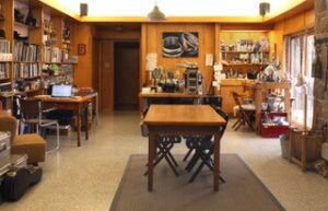 Interior view of Sandy MacFarlane's studio. Wooden book shelves with book and various work stations.