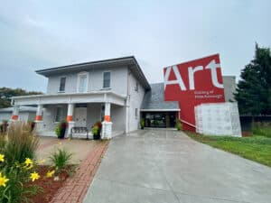 exterior of the Art Gallery of Peterborough. Four pillars that adorn the front porch are wrapped in orange ribbon