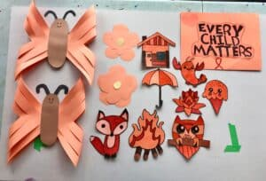 orange paper crafts featuring butterflies, flowers, foxes, owls and a sign that reads: Every Child Matters